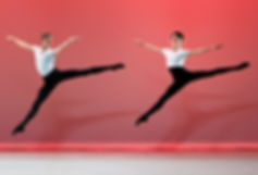 Bolshoi Ballet Academy Summer Intensive in New York final performance photo featuring two male dancers on stage in sissonne with a red backdrop.