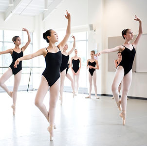 A group of dancers in black leotards in a studio in coupe derriere en pointe.
