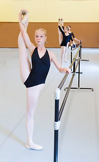 Female dancers at the barre stretching their legs in a la seconde.