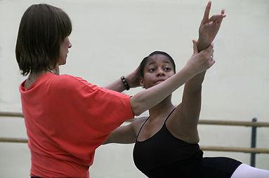 Bolshoi Ballet Academy teacher Svetlana Ivanova correcting the placement of a female dancer's arms and head in arabesque.
