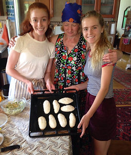 Two female NSLI-Y participants pose with their host family and pirozhki they baked together.