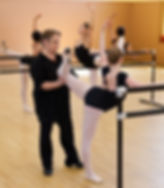 Bolshoi Ballet Academy teacher Natalya Revich correcting the position of a female dancer's knee in attitude derrière at the barre.