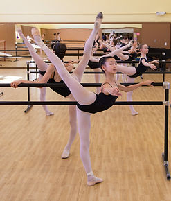 Female dancers in the studio at the barre in arabesque.