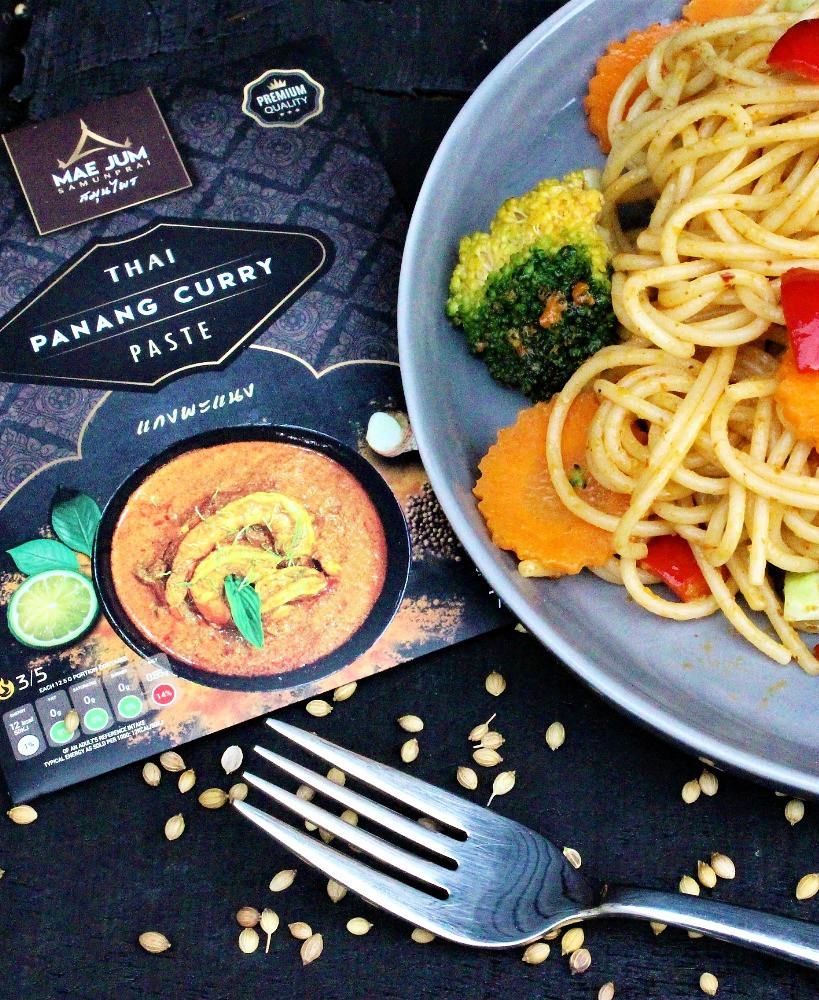 Panang Spaghetti on a plate with carrots, broccoli and red peppers and Mae Jum Thai Panang Curry Paste with fork