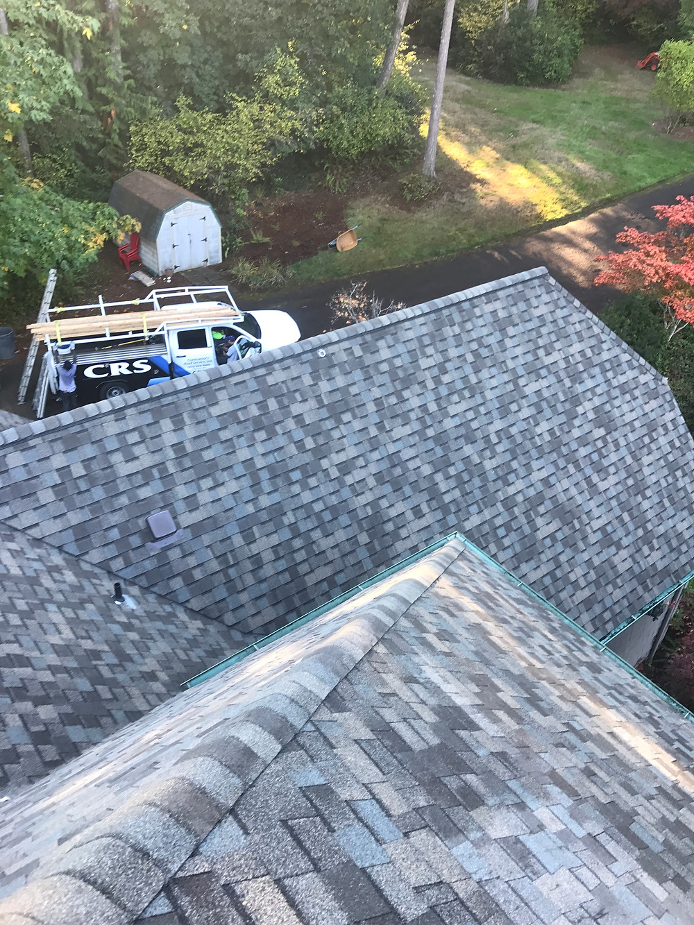 Example of home with roof covered in Asphalt shingles ranging from blue to grey with truck.