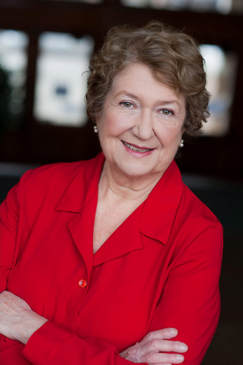 An older actress smiling and wearing a red top.
