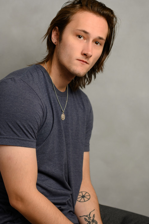 Headshot of a handsome actor with long hair and cool tattoos.