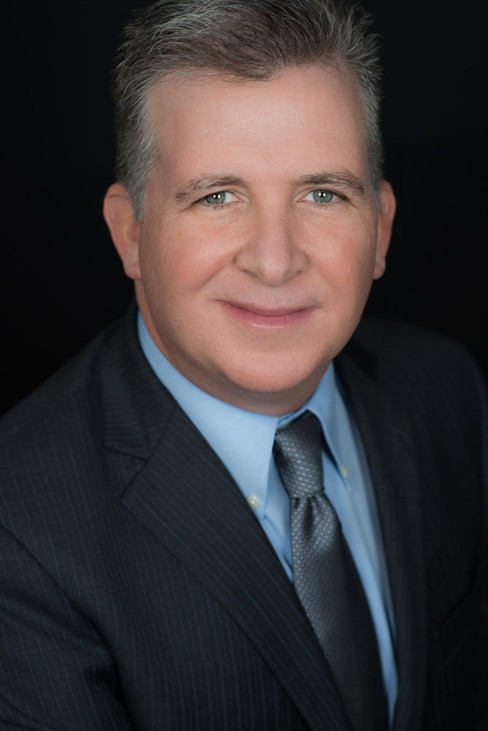 Formal corporate headshot of a man wearing a suit and smiling at the camera.
