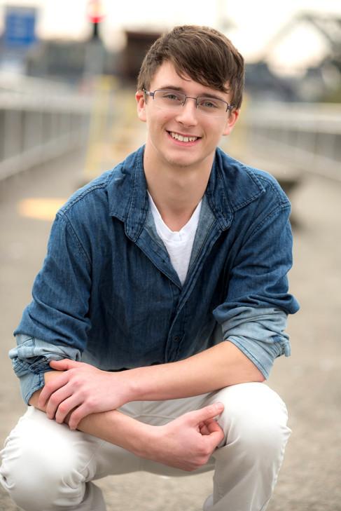 A teenage boy crouching down for a high school senior portrait.