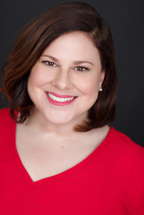 A terrific smiling headshot of a women in red.