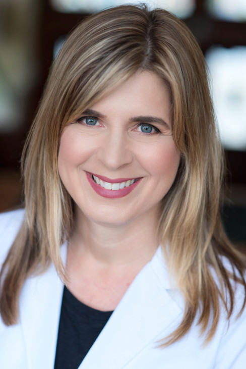 Professional doctors striking headshot in white lab coat.