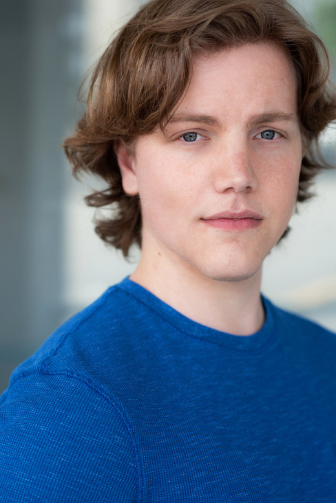 A serious headshot of a young actor wearing blue.