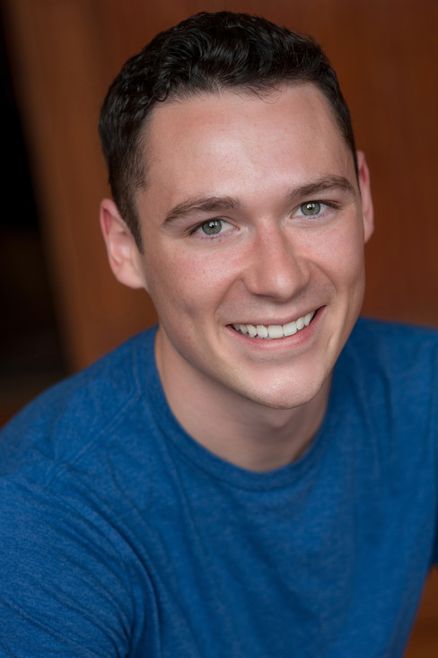 Great smiling headshot of a young actor wearing a blue t-shirt.