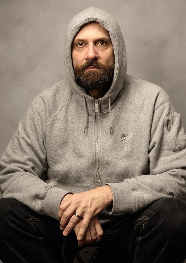 Hooded older man in sweatshirt looking d