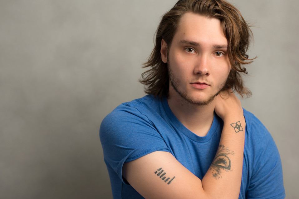 Great actor headshot of a guy with tattoos and great hair.