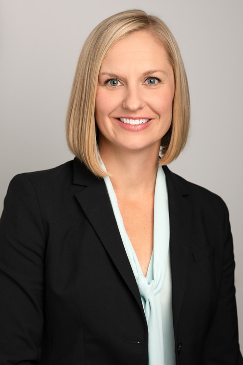 Professional corporate headshot of a beautiful wolman with short blonde hair.