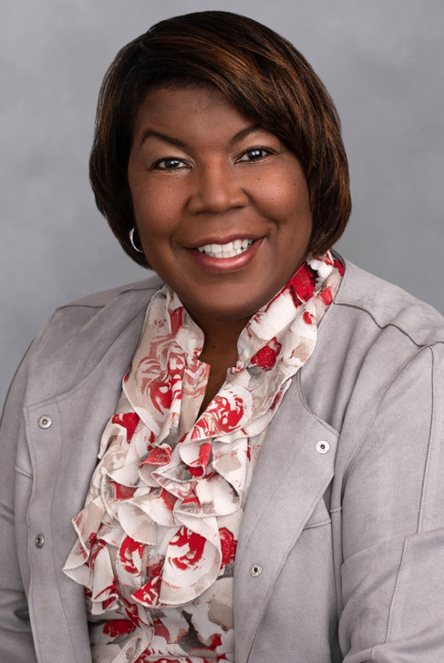 Lovely corporate headshot of a businesswoman wearing a ruffled top and gray jacket.