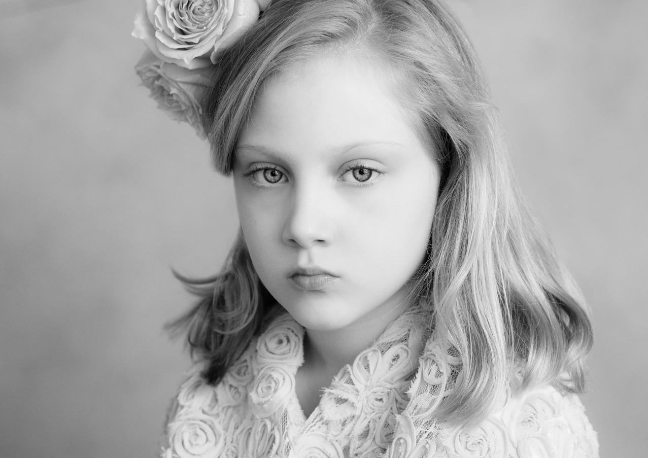 Classic black and white portrait of a young girl with a flower in her hair.