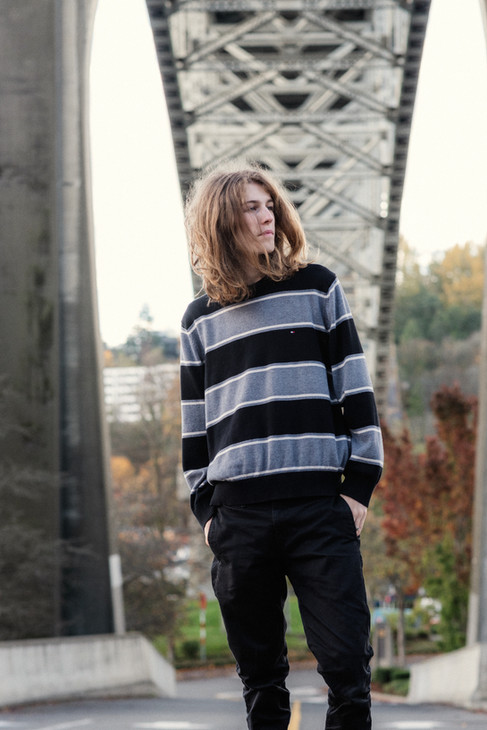 High School senior portrait of a young man with long hair standing under a bridge.