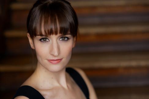 Fabulous headshot of an actress with dark hair and bangs.