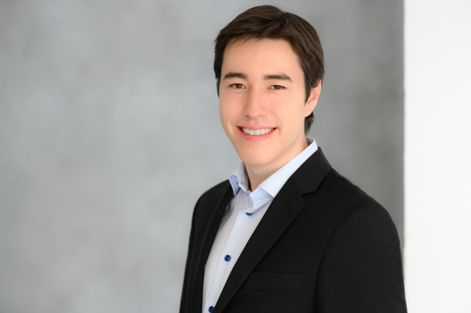 Awesome corporate headshot of a young man smiling at the camera.
