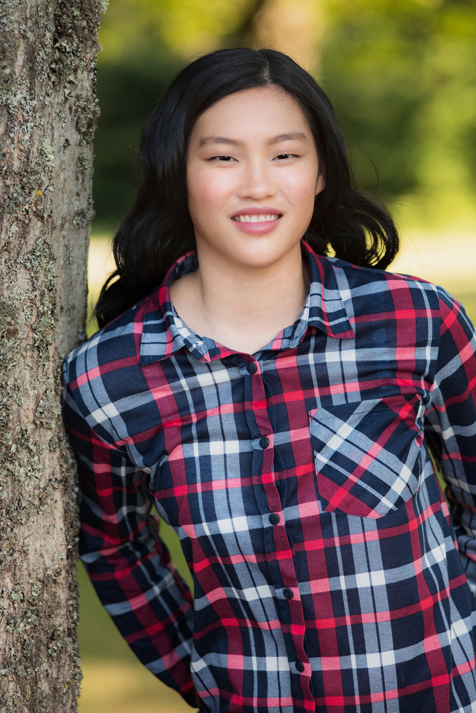 High school senior wearing a plaid shirt leaning against a tree.