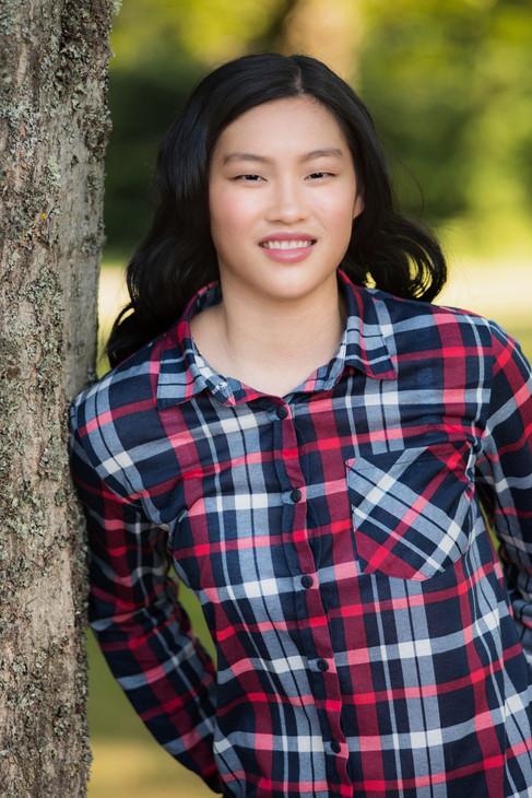 High school senior wearing a plaid shirt leaning against a tree.