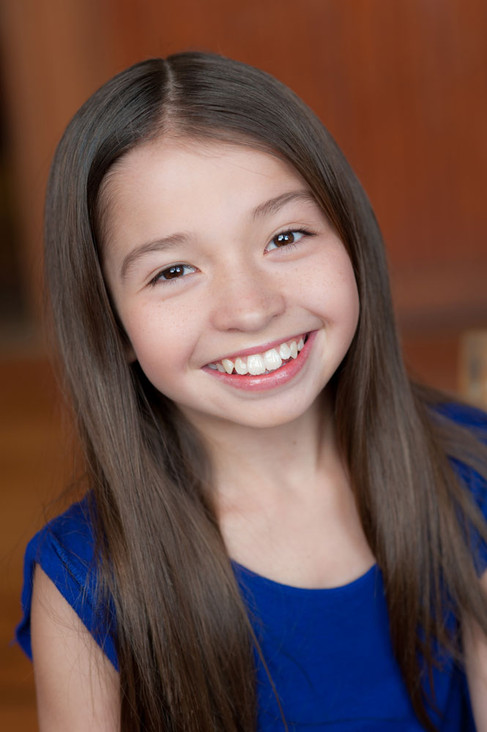 Super fun headshot of a young girl with a fabulous smile.