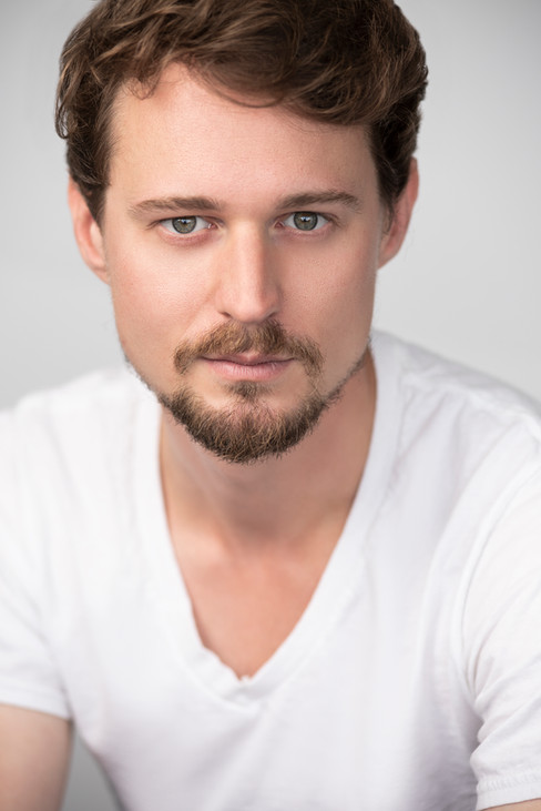 A headshot of an actor wearing a white v-neck t-shirt and an intense look.