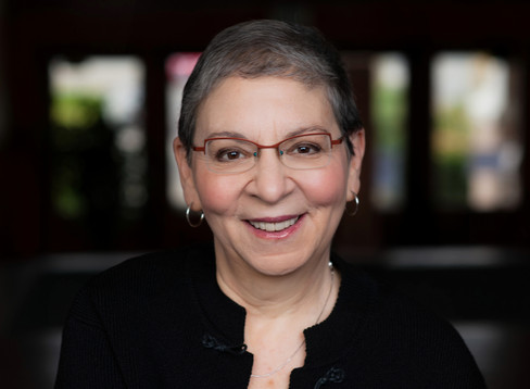 Vibrant headshot of an author wearing glasses and smiling.