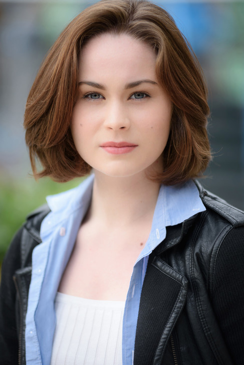 A natural light headshot of an actress with blue eyes.