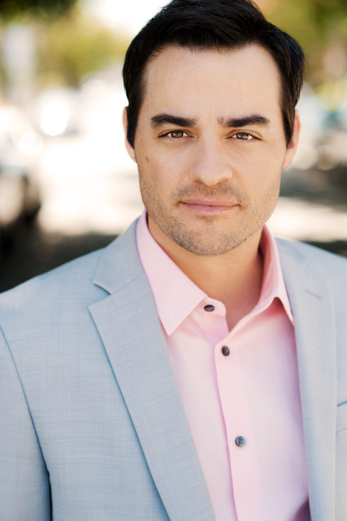 Natural light corporate headshot of a man wearing a light colored suit and pink shirt.