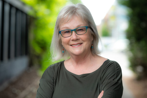 Professional headshot of an older woman wearing glasses and a great smile.