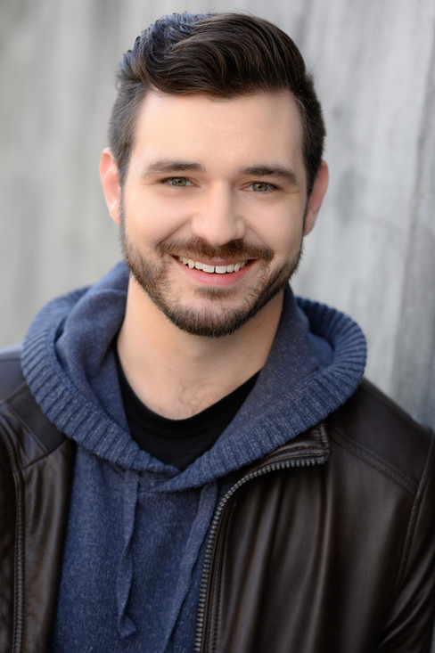 Seattle commercial actor headshot of guy smiling in blue hoodie and leather jacket.