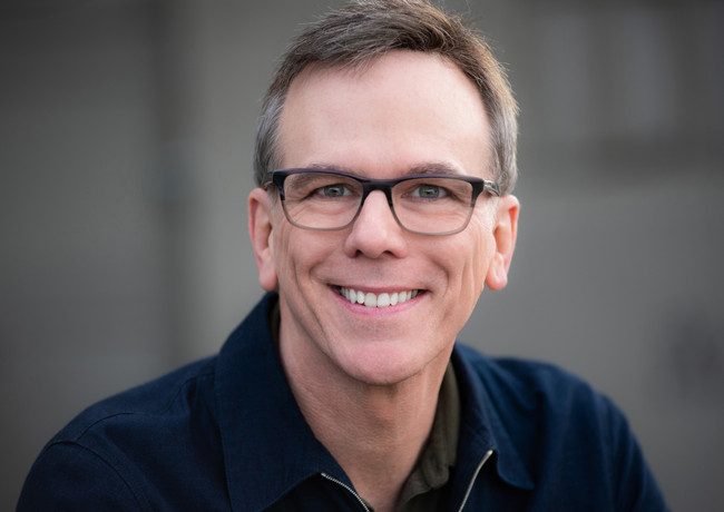 Smiling headshot of an actor wearing gla