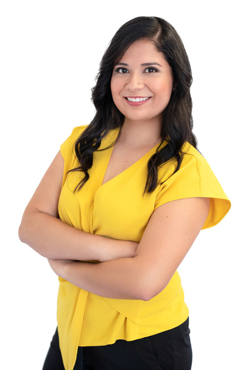 Strong realtor headshot of a woman staing with her arms crossed wearing a yellow blouse.
