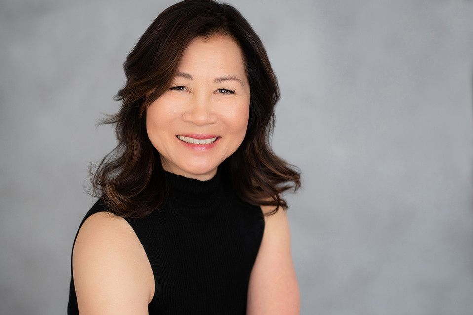 Awesome corporate headshot of a woman wearing a tank top and smiling.