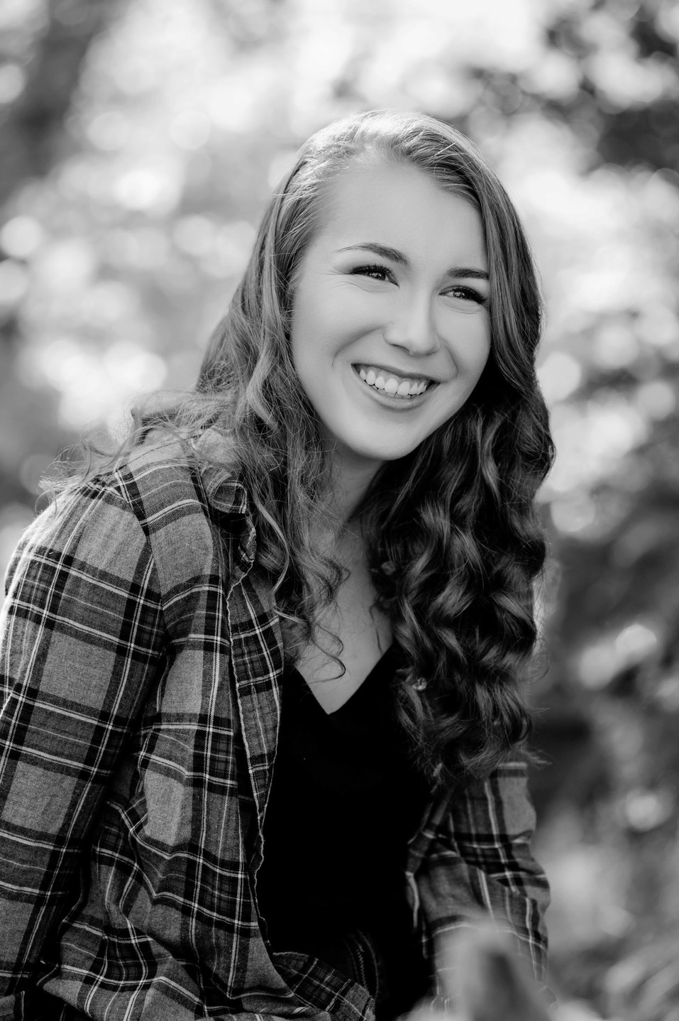 A great smiling senior high school picture in black and white of a teenage girl.