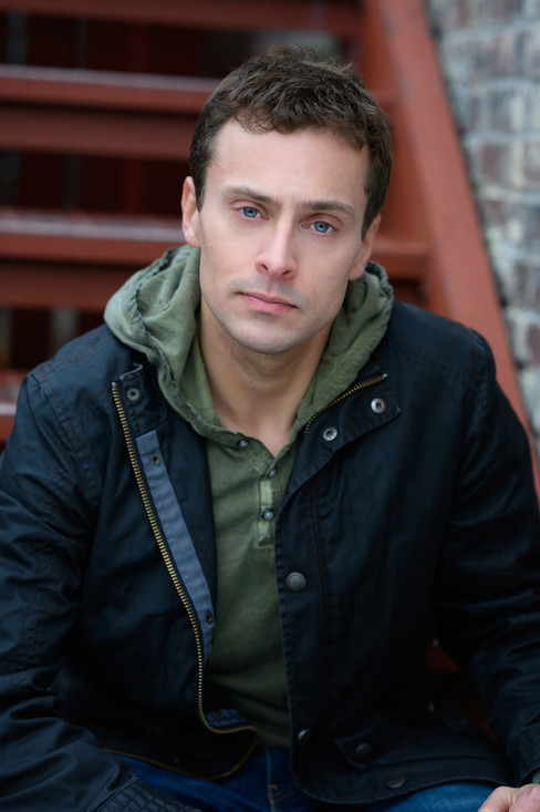 Great headshot of a man wearing a leather coat with blue eyes.
