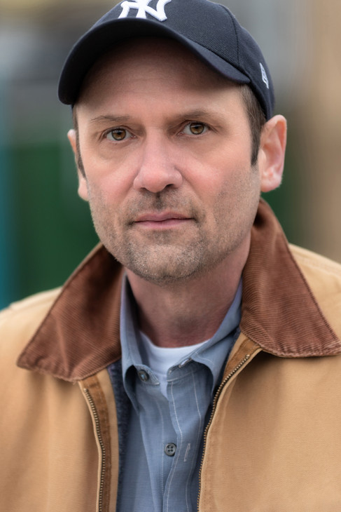 Rugged actor headshot of a man wearing a baseb
