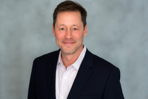 Wonderful corporate headshot of a man in a sports jacket smiling at the camera.
