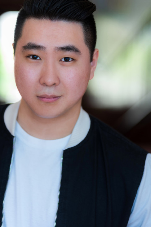 Professional actors headshot of a man in a white t-shirt and jacket.