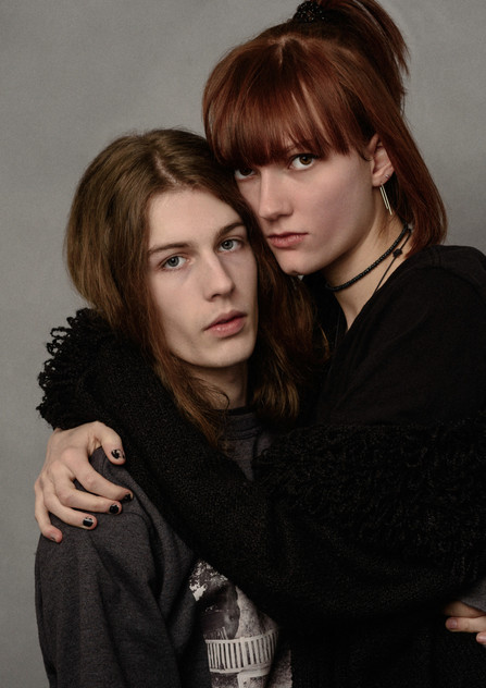 Great portrait of a young couple hugging and looking very serious.