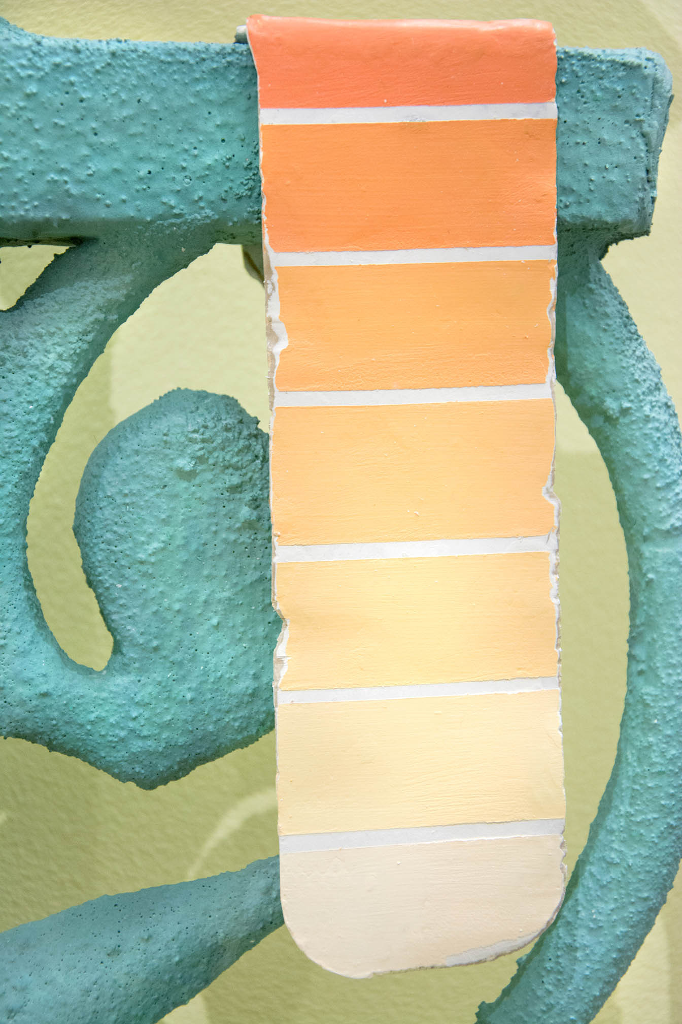SV Randall, Textured sculpture titled, Rose Colored Lenses of ornate green baroque fence segment on a curved yellow pedestal with sculpted orange paint swatches as part of a contemporary art exhibition.