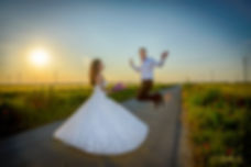 Bride and groom on road in a field at sunset
