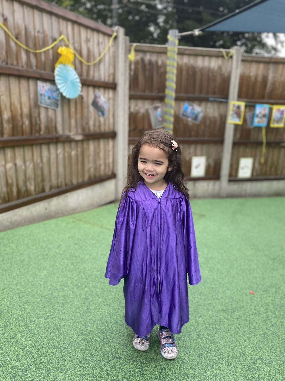 Gabby smiling and wearing a purple robe for her graduation day.