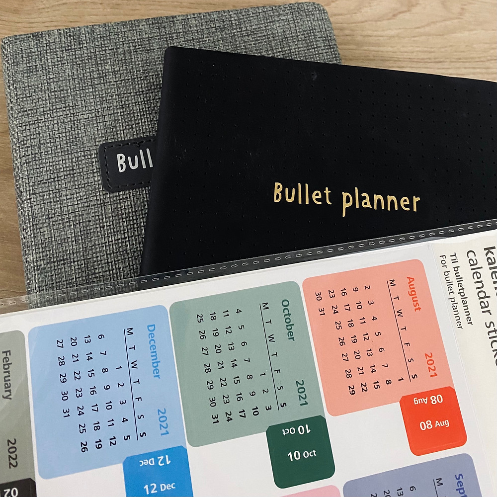 Two bullet journals and calendar stickers for the journal.