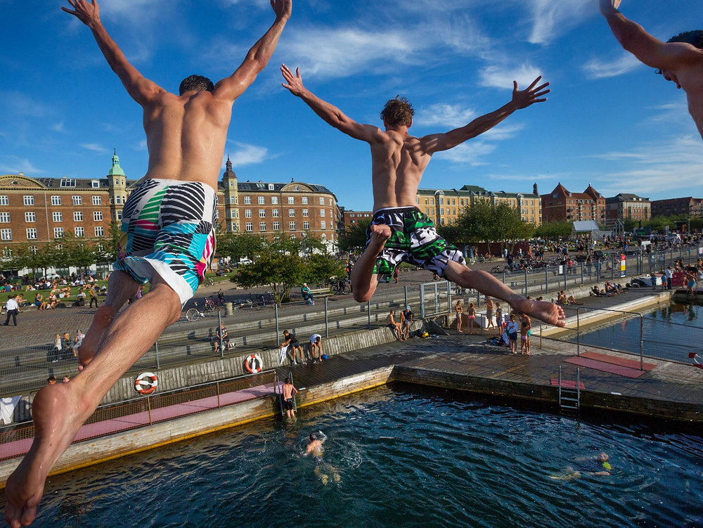 young men leap from a 16-foot-high diving platform into Copenhagen's harbor