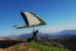 A graduated student flies off the mountaintop solo for the first time under radio guidenace from a hang glidng instructor in the landing zone