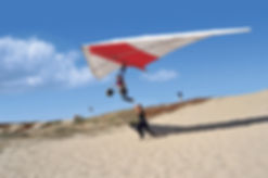 Hang Gliding Instructor runs next to a new student as they learn to fly